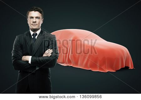Businessman with crossed arms standing in front of car covered with red veil on dark background. Car developer presenting new product