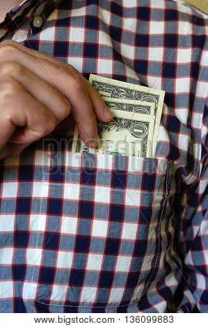 Dollars in the shirt pocket and man's hand