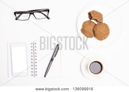 Top view of office desktop with blank white cellular phone notepad and pen coffee cup cookies on plate and glasses. Mock up