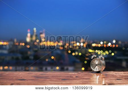Closeup of wooden table with alarm clock on blurry night city background
