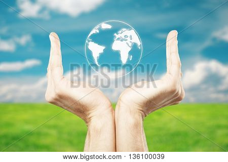 Male hands holding abstract terrestrial globe on beautiful landscape background