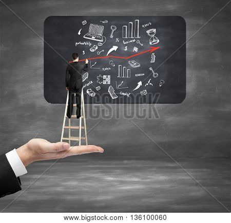 Hand holding ladder with businessman drawing business sketch on chalkboard in room. Success concept