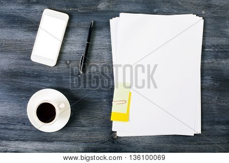 Top view of wooden table with blank paper sheet white smartphone pen and coffee cup. Mock up