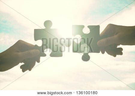 Partnership concept with hands putting jigsaw pieces together on sky background with sunlight