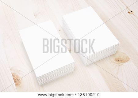 Two stacks of blank business cards on light wooden surface. Mock up 3D Rendering