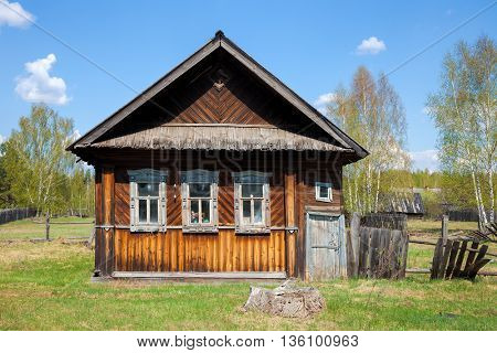 Old weathered log house and in a village