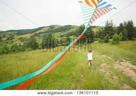Little boy running with kite in countryside