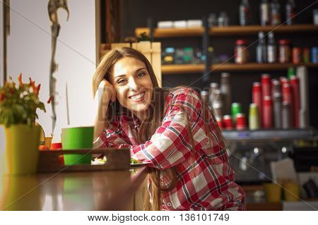 Toned image of happy smiling beautiful lady looking at camera while sitting in cafe or restaurant. Lady waiting for someone.