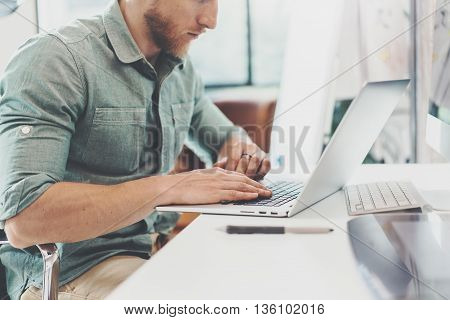 Bearded Hipster Working Table Laptop Modern Interior Design Loft Office.Man Work Coworking Studio, Use contemporary Notebook, typing keyboard.Blurred Background.Creative Business Startup Idea.Horizontal