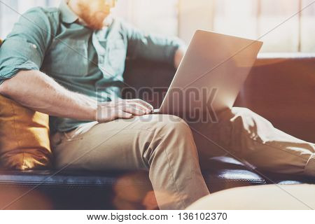 Bearded Style Businessman work Laptop modern Interior Design Loft Studio office.Man chilling Vintage chair.Use contemporary Notebook, blurred background.Creative Process New Startup Idea.Flares effect