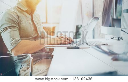Bearded Hipster Working wood Table Laptop Modern Interior Design Loft Office.Man Work Coworking Studio, Use contemporary Notebook.Blurred Background.Creative Business Startup Idea.Flares, film effect
