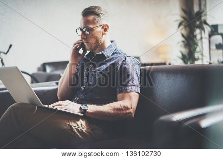 Successful Risk Manager working Laptop modern Interior Design Loft Office.Man work Vintage Sofa, Using contemporary Smartphone Hand Calling.Blurred Background.Business Startup Idea Process.Film effect