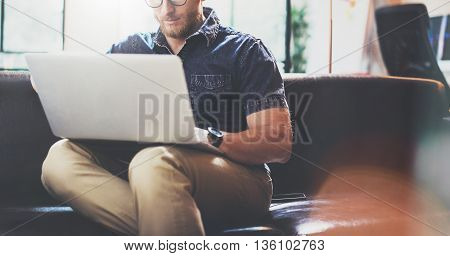 Successful Trade Broker working Laptop modern Interior Design Loft Office.Man work Vintage Sofa, Use contemporary Notebook, Browsing Internet.Blurred Background.Business Startup Idea Process.Horizontal