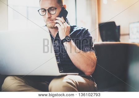Bearded Hipster Working Laptop Modern Interior Design Loft Office.Intelligent Man Sitting Vintage Sofa.Using contemporary Smartphone Hand.Blurred Background.Creative Business Startup Process Idea.Film