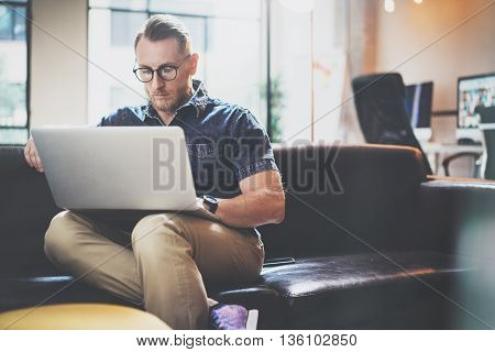 Bearded Style Businessman work Laptop modern Interior Design Loft Studio office.Guy Relaxing Vintage chair.Use contemporary Notebook, blurred background.Creative Process New Startup Idea.Film effect