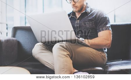 Successful Trade Manager working Laptop modern Interior Design Loft Office.Men work Vintage Sofa, Use contemporary Notebook, Browsing Internet.Blurred Background.Business Startup Idea Process.Horizontal