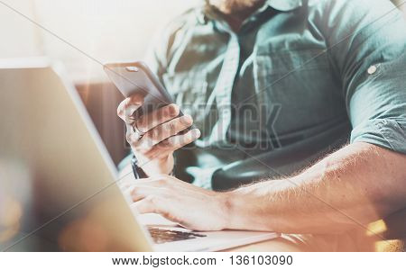 Bearded Businessman work Laptop modern Design Interior Loft Studio.Men Lounge Vintage Sofa.Use contemporary Notebook Send MessageMobile Phone.Blurred background.Creative Process Startup Idea.Film