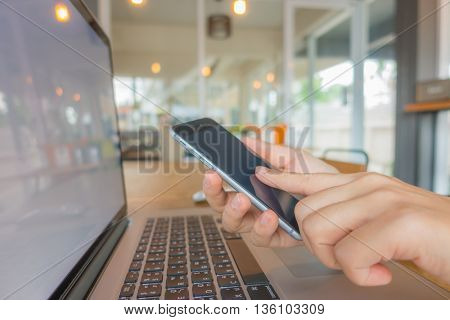 Closeup of business woman hand typing on laptop keyboard with mobile phone