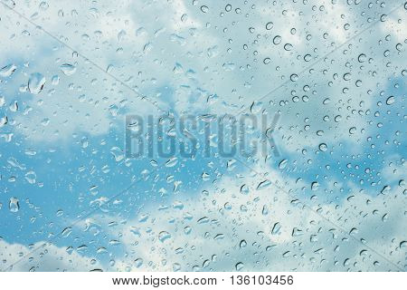 Drops of water on glass window over blue sky