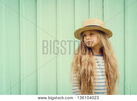 Cute little girl stands near a turquoise wall in boater hat and pensively looks aside. Space for text. Negative space.