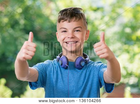 Portrait of a teen boy 12-14 year old showing thumbs up gesture. Teen boy with headphones and sunglasses posing outdoors.