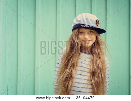Cute little girl stands near a turquoise wall in sailor hat and smiling Space for text. Negative space.