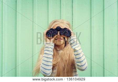 Cute little girl stands near a turquoise wall and looks binoculars. Space for text.Negative speace.