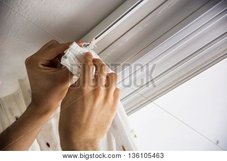 Hands of man or handyman installing curtains over window at home, doing renovation work