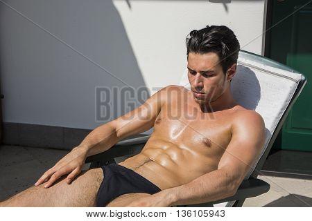 Shirtless Young Man Drying Off in Hot Sun, Muscular Man Wearing Bathing Suit Sunbathing on Beach Lounge Chair