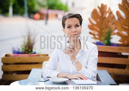 Elegant beautiful woman with notebook drinking coffee at cafe.
