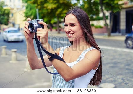 Portrait of attractive lady in overalls taking a picture while walking around the town