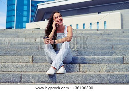 Attractive woman having a cheerful talk on the phone while drinking coffee on fresh air