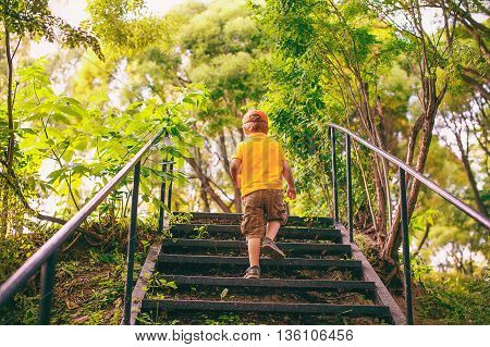 kid goes up the stairs in the park. concept of growing up. step by step the child rises higher and goes farther