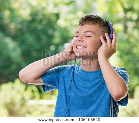 Teen boy smiling listening a music in headphones, posing outdoors.