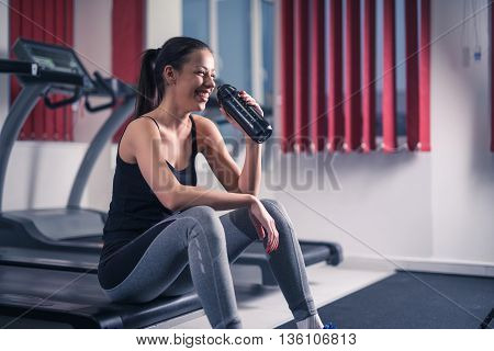 Woman drinking water after exercising in the gym.