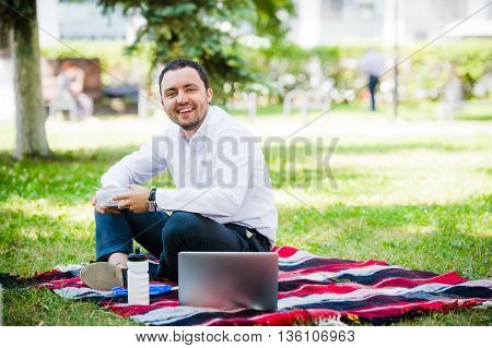 Young and attractive man relaxes in the park at lunch time.