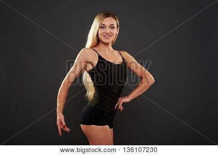 Beautiful athletic woman with long blond hair is posing in black sportswear isolated over black background