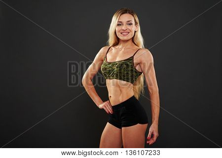 Young sexy muscular woman posing with one hand on hip isolated over black background