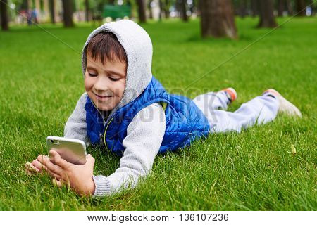 Small boy in jacket with hood is lying on green grass in park and using smart phone