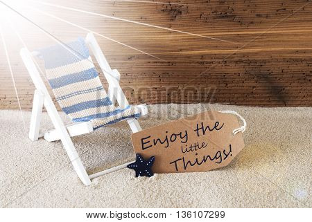Sunny Summer Label With Sand And Aged Wooden Background. English Quote Enjoy The Little Things. Deck Chair For Holiday Or Vacation Feeling.