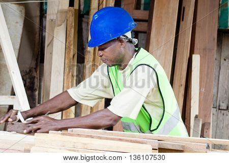 The carpenter planes wood for making his furniture.