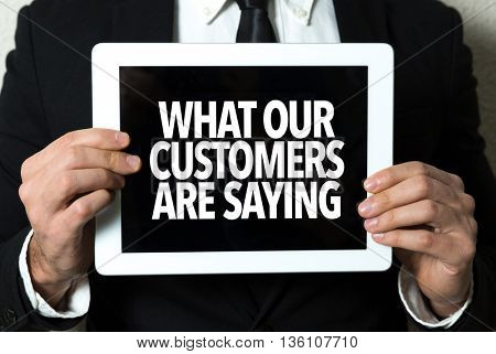 Business man holding a tablet with the text: What Our Customers Are Saying