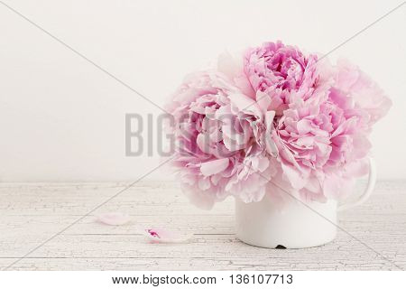 pink peonies in an old enamel mug, soft vintage effect, copyspace