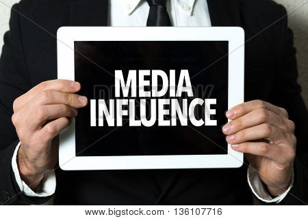 Business man holding a tablet with the text: Media Influence