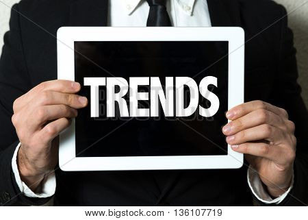 Business man holding a tablet with the text: Trends