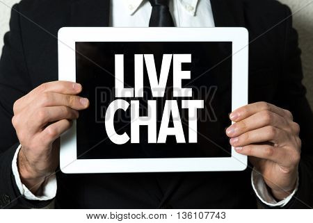 Business man holding a tablet with the text: Live Chat