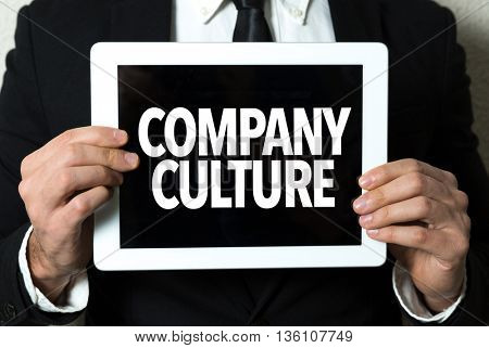 Business man holding a tablet with the text: Company Culture