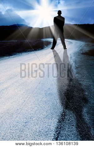 conceptual image of a man standing agains the sun rays