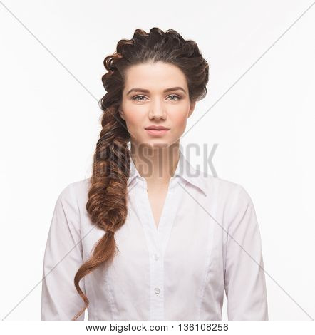 Hair braids style. Beautiful woman with modern hairstyle posing isolated on white background. Lady in white blouse in studio.