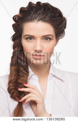Creative braid hairstyle. Beautiful woman looking at camera and demonstrating her gorgeous brown hair isolated on white background.